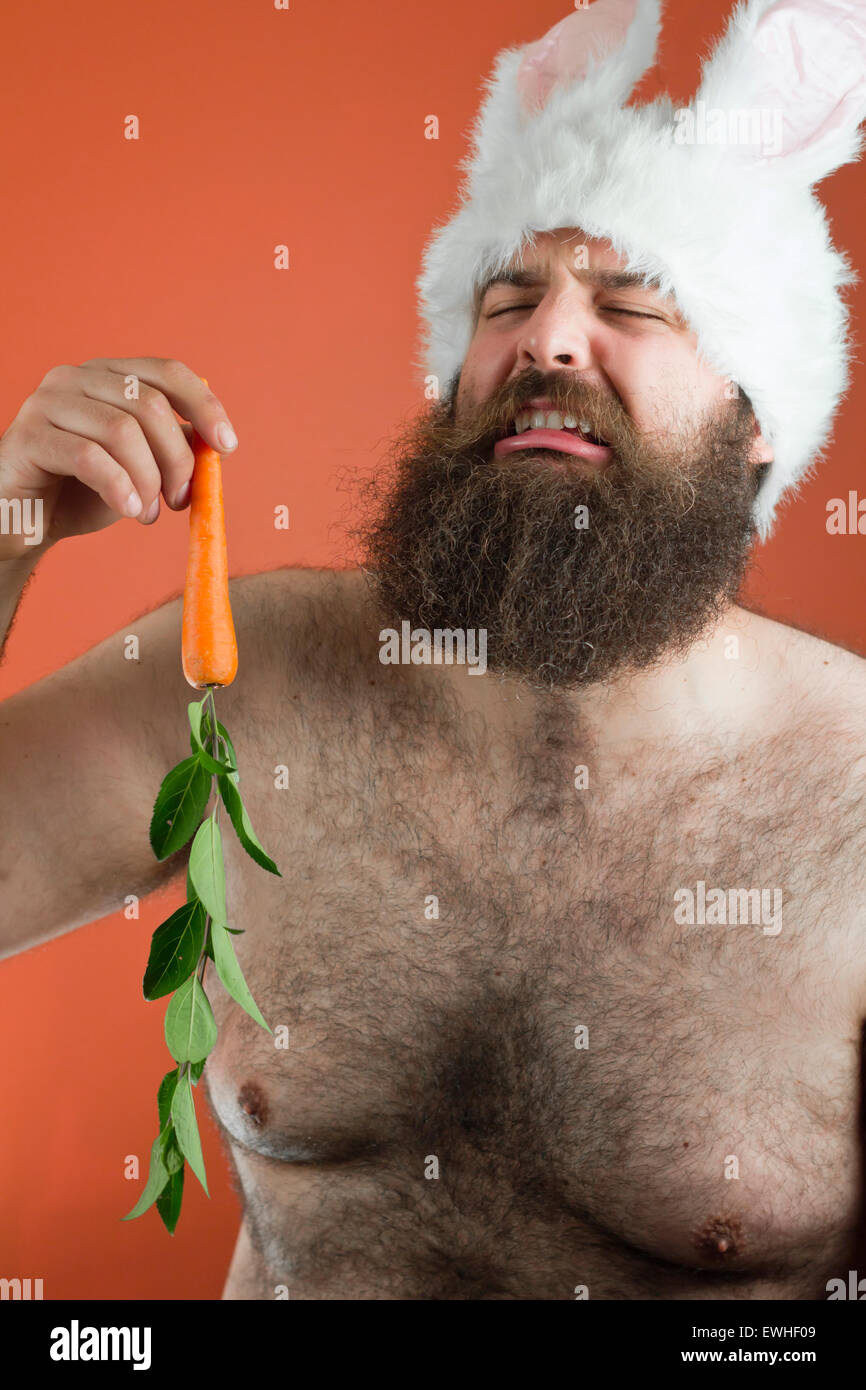 Crying bearded fat man wears silly bunny ears - Stock Image
