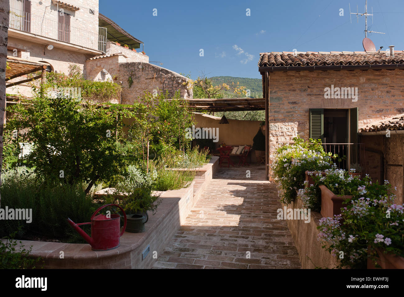 Umbrian brick paved courtyard with raised beds - Stock Image