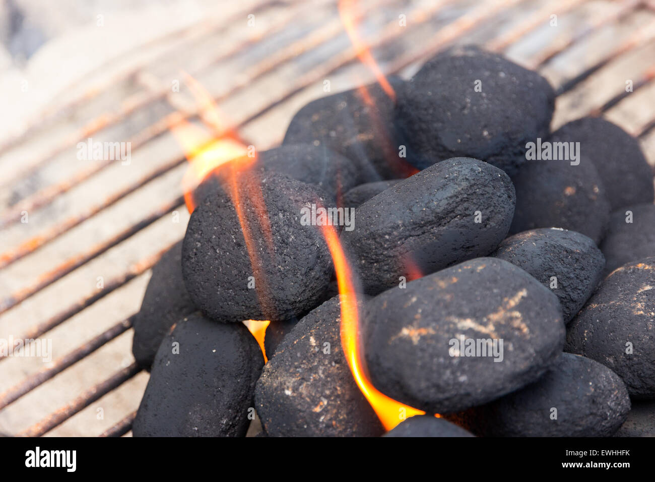 Charcoal briquettes on fire in a BBQ - Stock Image