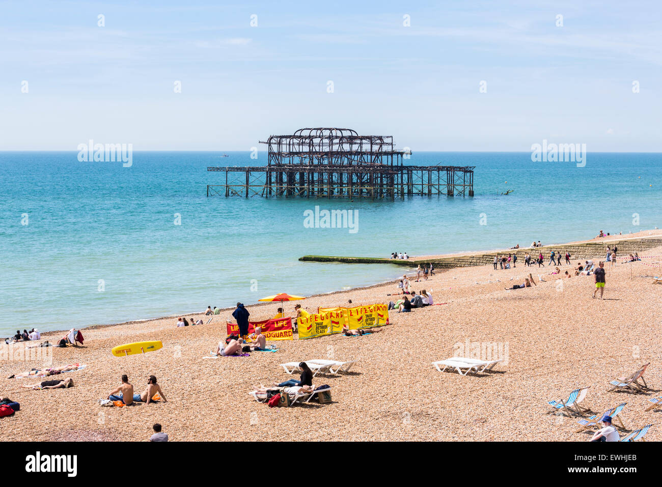 The burnt-out frame of the Victorian West Pier at Brighton, East Sussex, UK, lifeguards stationed on the beach - Stock Image
