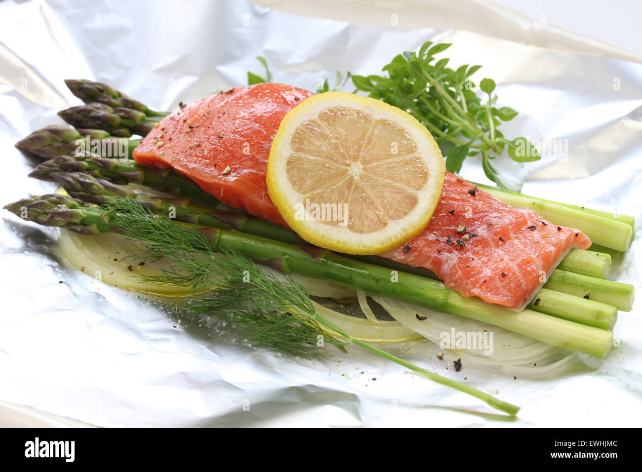 fresh salmon with asparagus in foil paper, ready for cooking - Stock Image