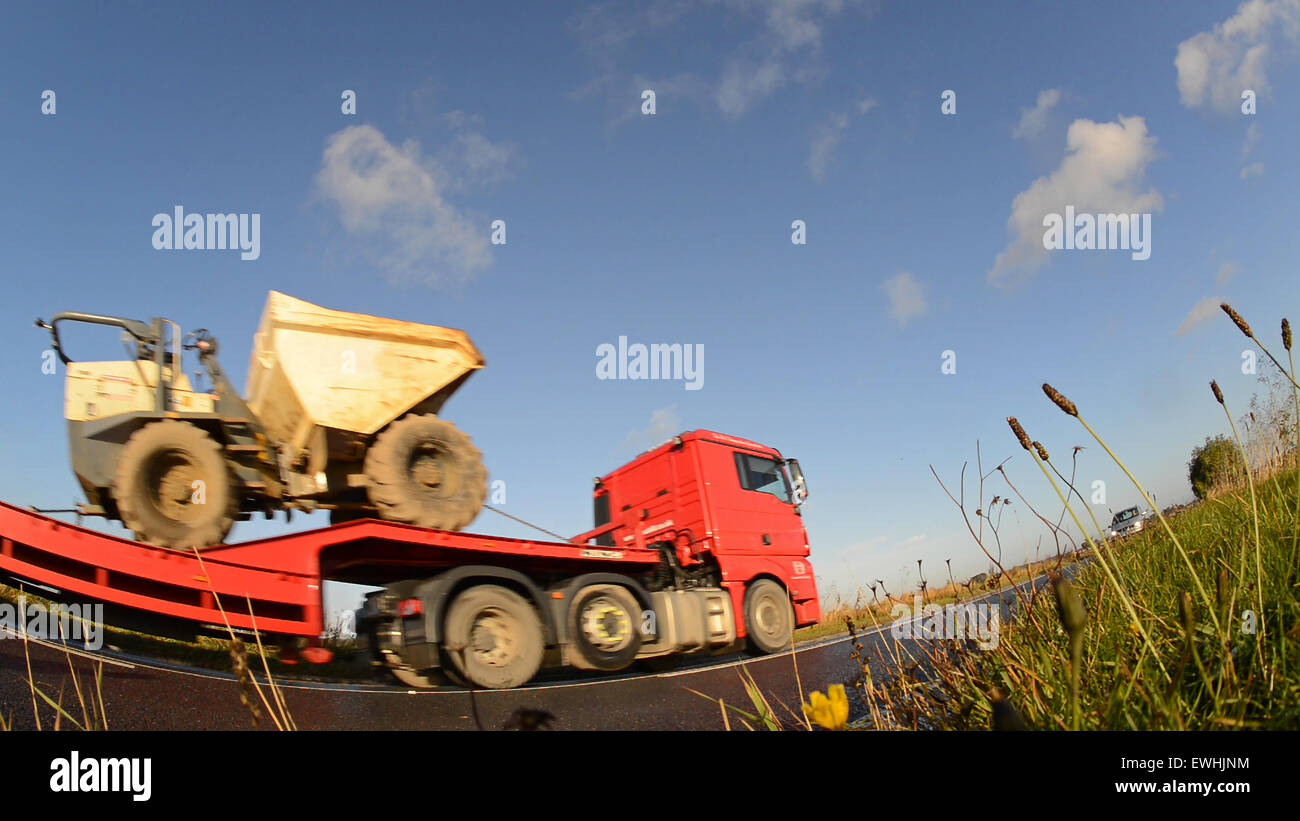 worms eye view of articulated low loader lorry traveling on country road near leeds yorkshire uk Stock Photo