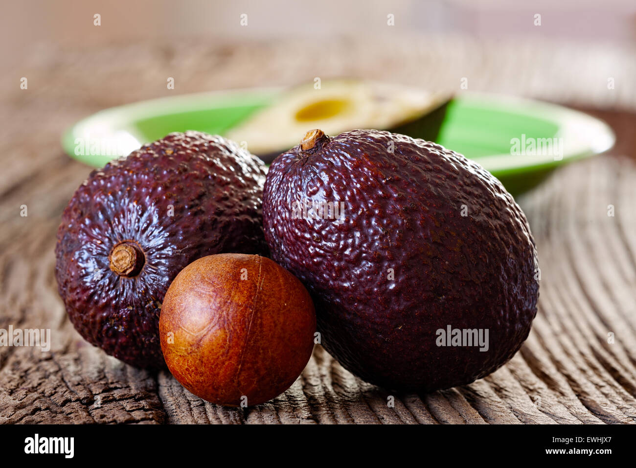 Two ripe avocados and avocado core on an old rustic wooden plank - Stock Image