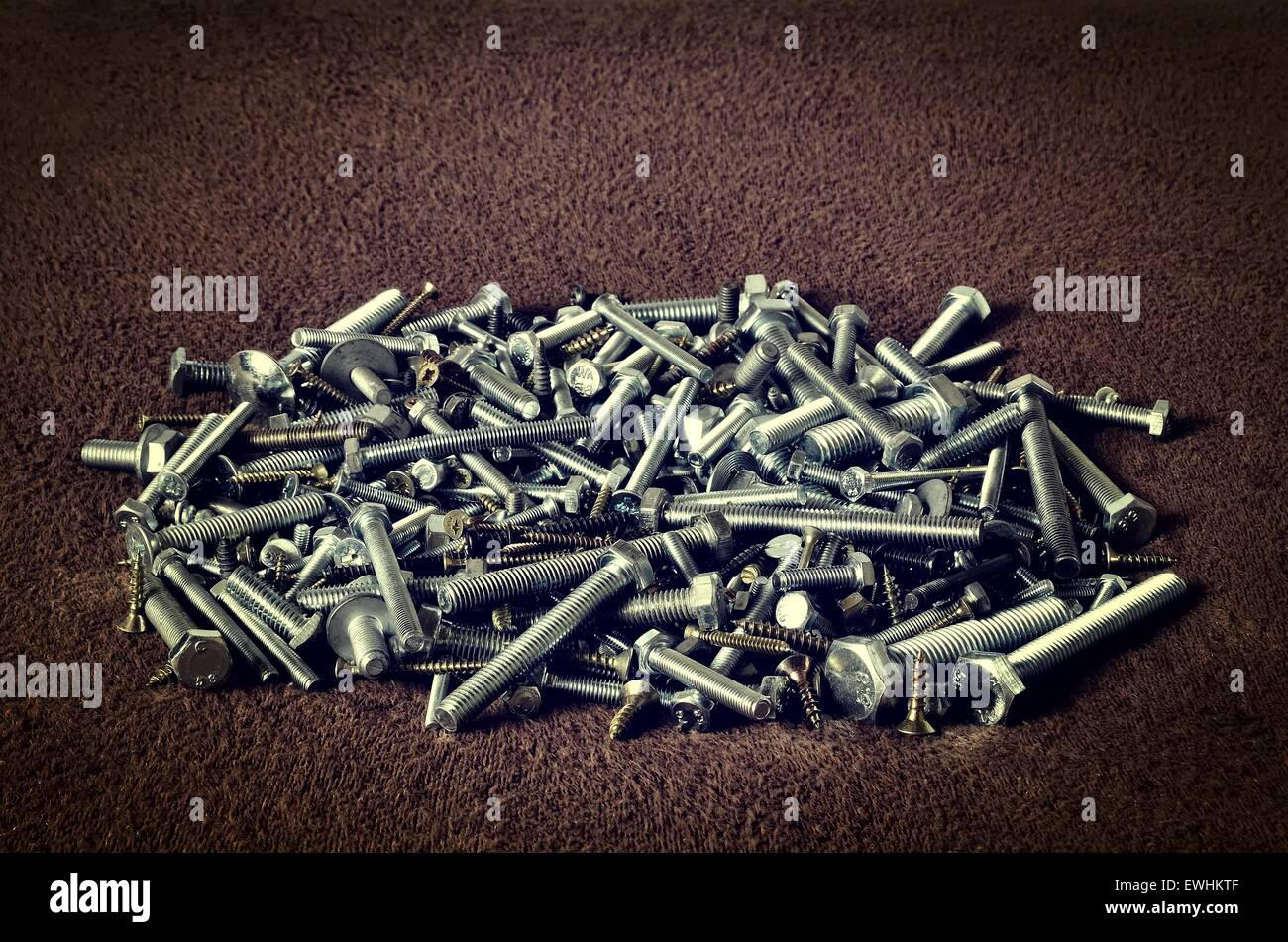 Group of screws. Bolts, nuts, screws in a pile on dark background. Stock Photo