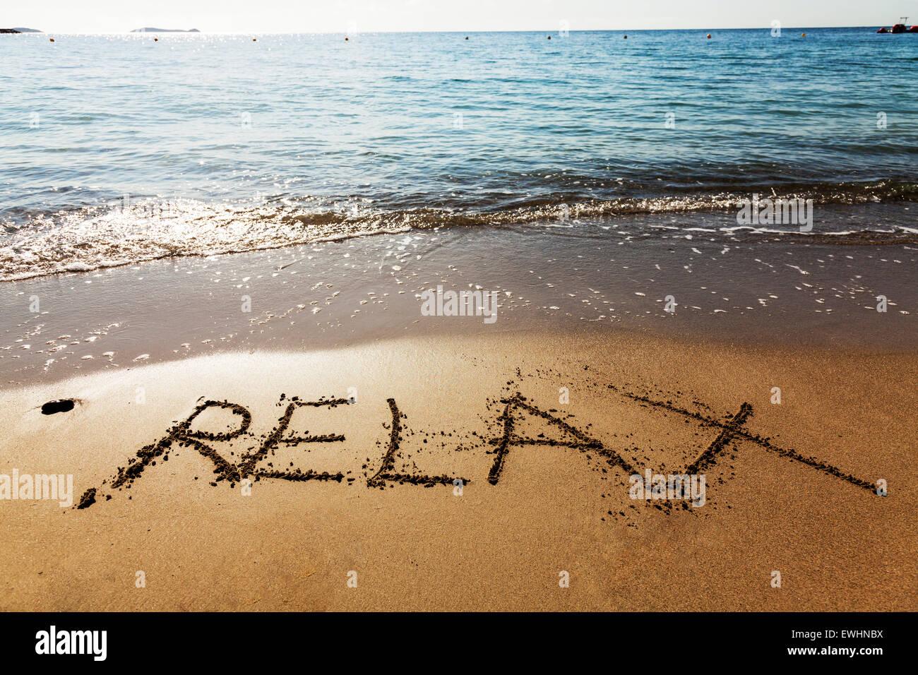 Relax in sand word written on beach coast chill holiday getaway sea coastline Ibiza Spain Spanish Santa Eulalia Stock Photo