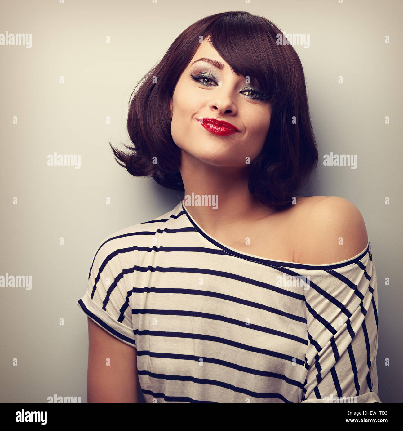 Pretty young woman grimacing with short black hair style in fashion blouse. Vintage closeup portrait Stock Photo