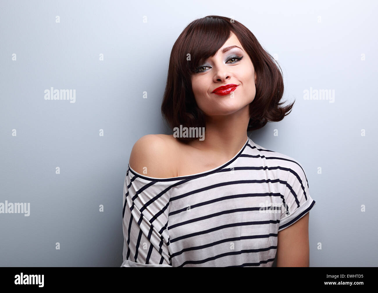 Funny young woman grimacing with short black hair style on black background Stock Photo