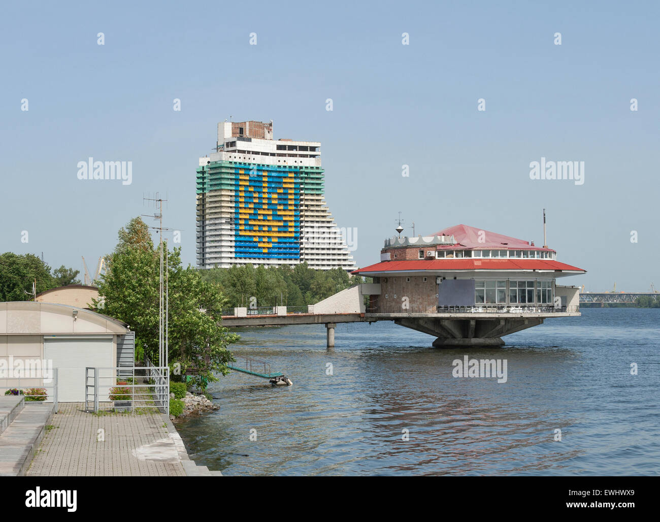 Dnipropetrovsk cityscape witn Dnieper river and coat of arms of Ukraine performed on the facade of the unfinished - Stock Image
