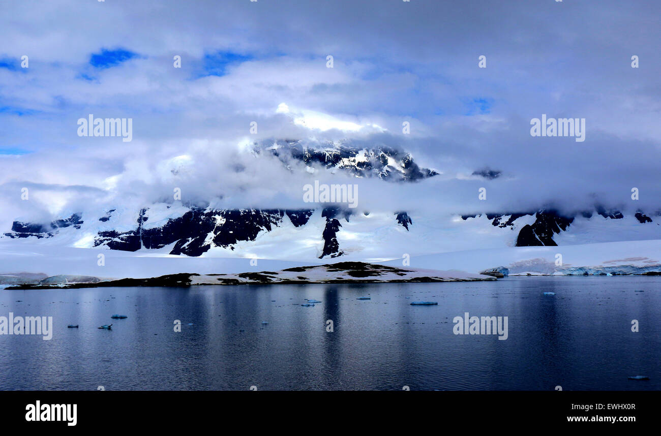 A majestic mountain peaks out behind low cloud as a small ship skirts around the icy island below. - Stock Image
