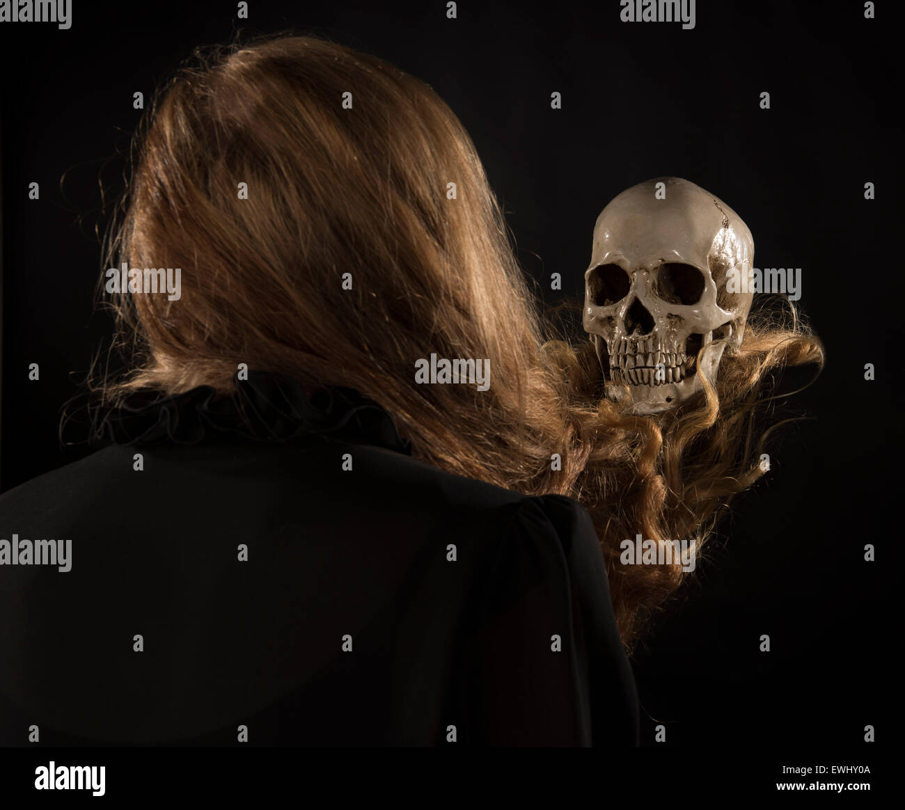 Woman with Blond Hair Holding Skull - Stock Image