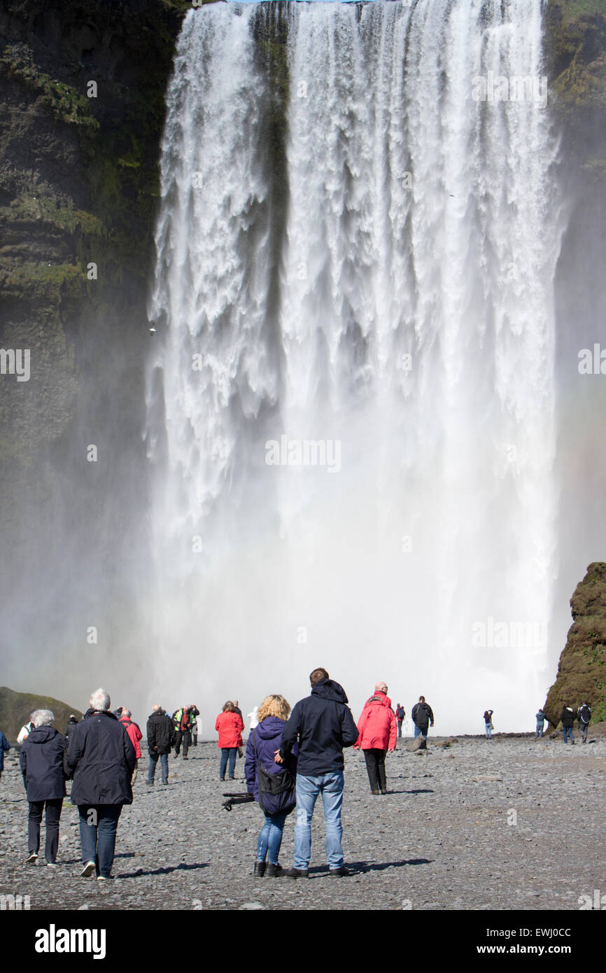 crowds of tourists at skogafoss waterfall in iceland - Stock Image