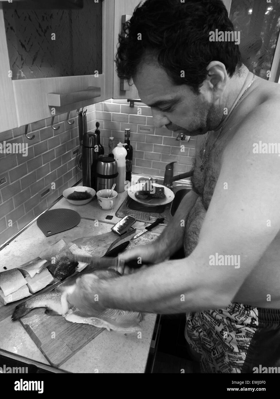 June 13, 2015 - Caucasian middle-aged man in shorts cleans fish trout in the kitchen. Series real people © - Stock Image