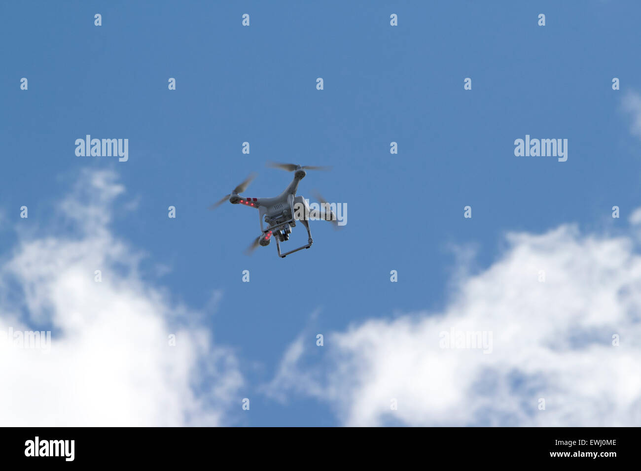 dji phantom remote drone camera flying against blue sky - Stock Image