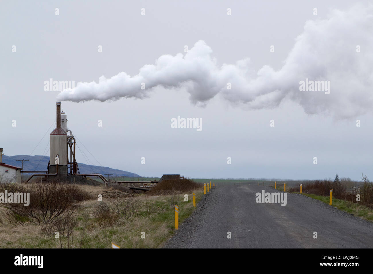 small rural community geothermal energy plant steam blowing over rural gravel road southern iceland - Stock Image