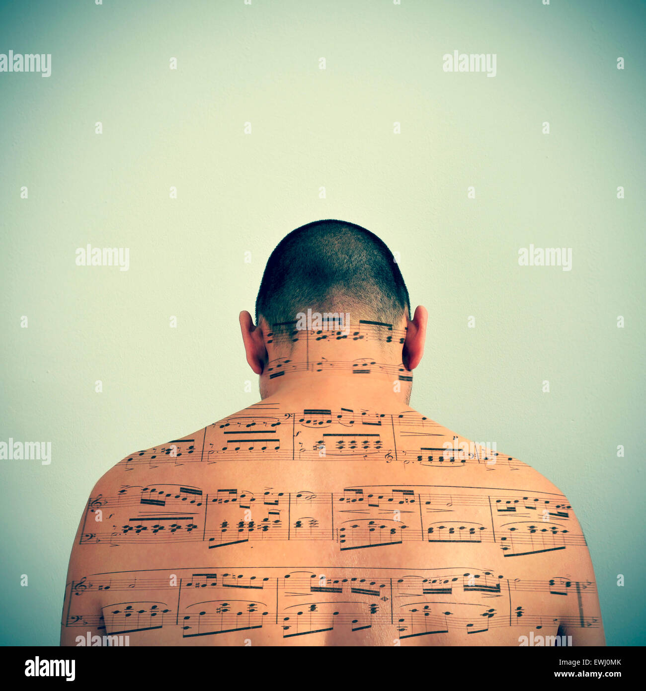 a young caucasian man with a musical score patterned in his back, with a retro effect - Stock Image