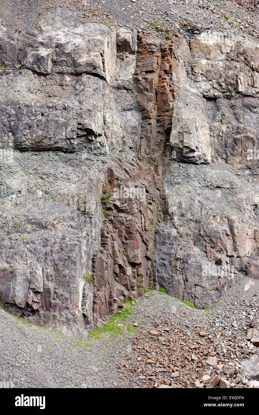 basalt dyke rock formations formed by magma hardening in rock fractures in the hillside Iceland - Stock Image