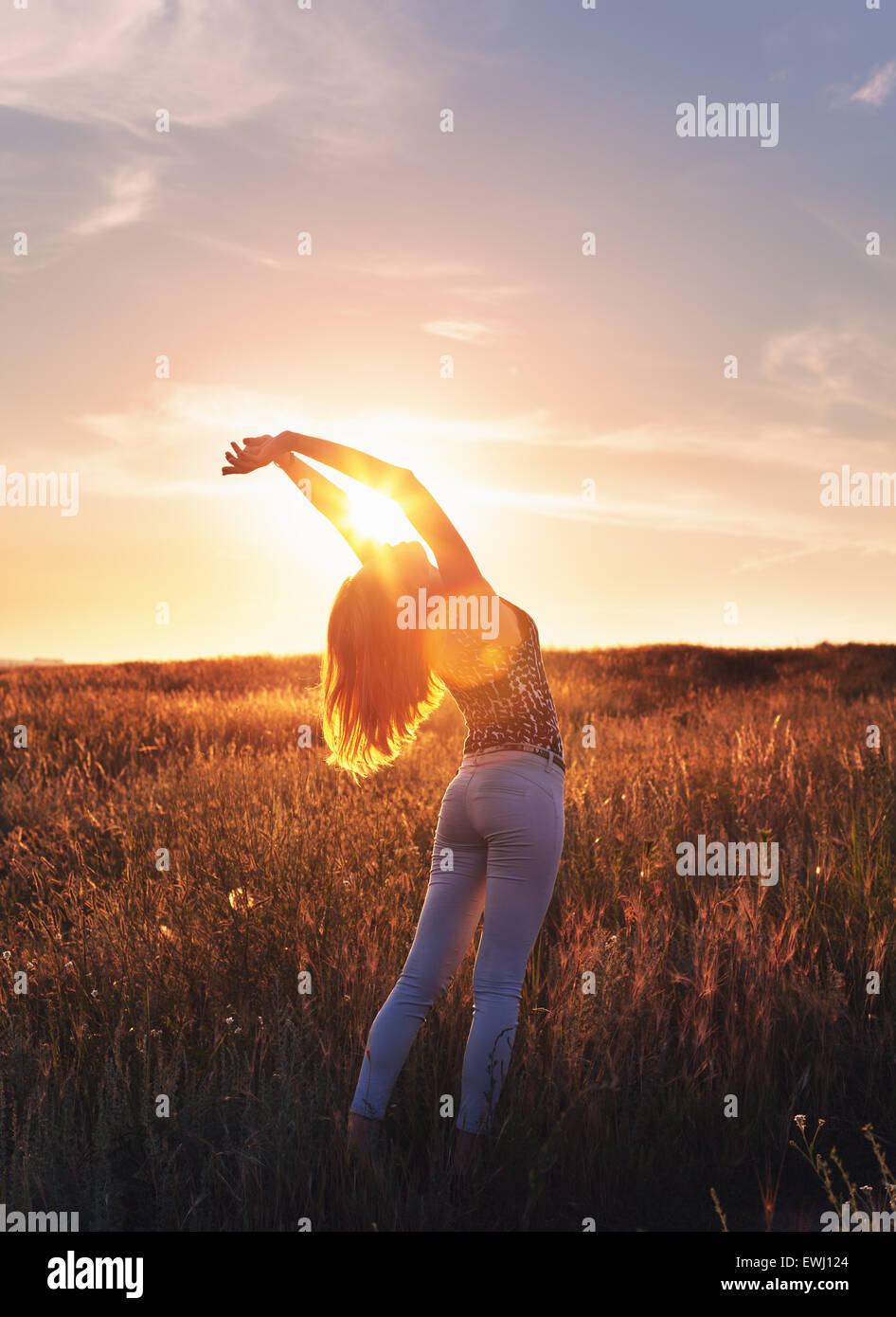 Free happy young woman raising arms at sunset in the field in summer. Background Stock Photo