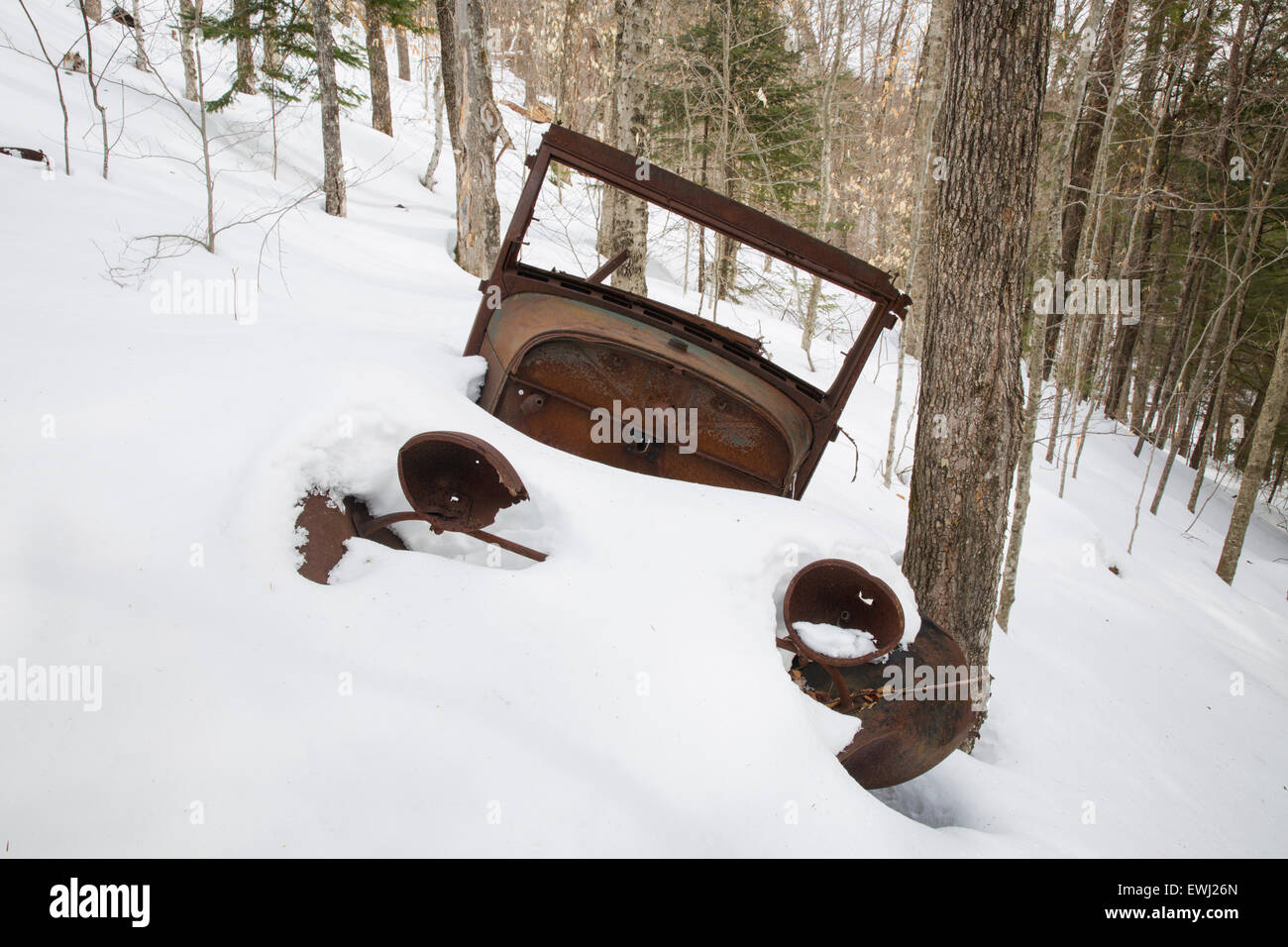 Rusted car in the Eastman Brook drainage of Thornton, New Hampshire USA during the winter months. This is possibly - Stock Image