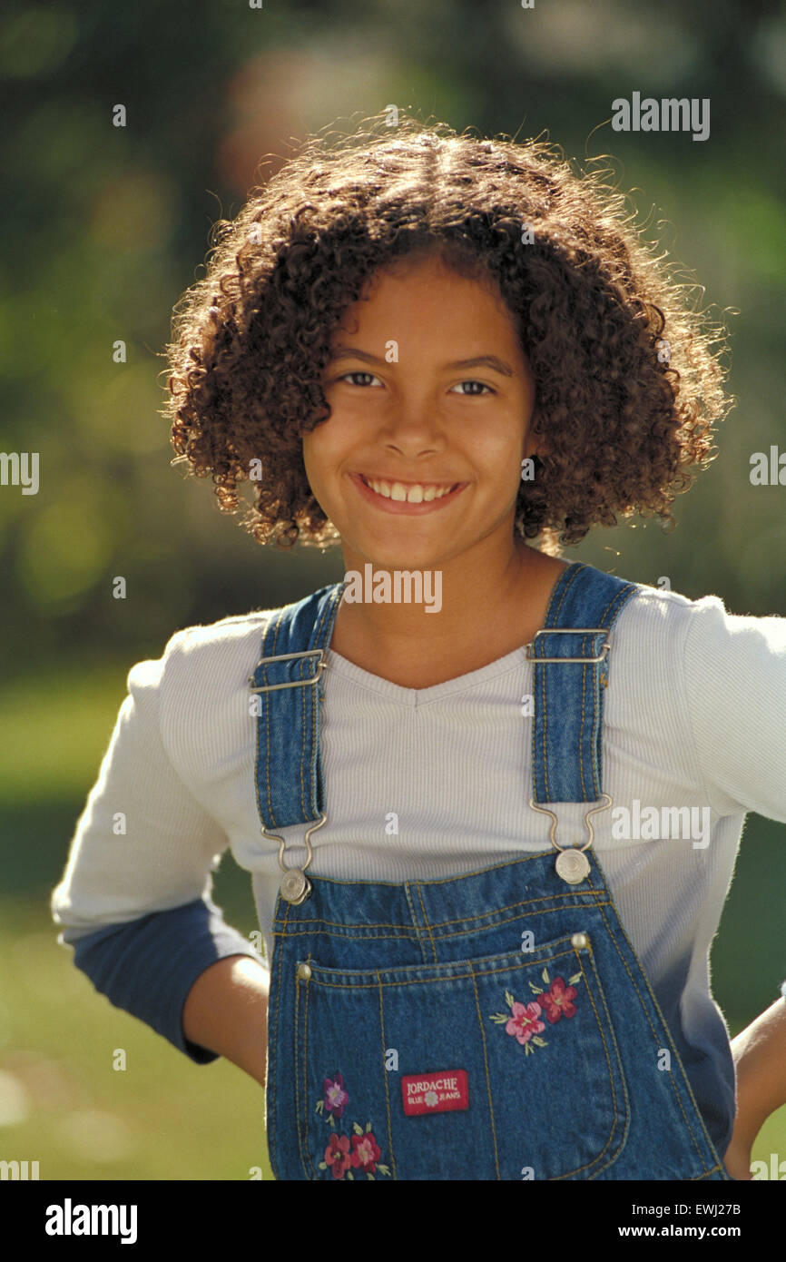 Portrait Of A Pretty Biracial Girl With Curly Hair Looking At The Camera And