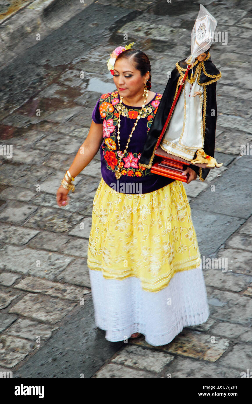 Mexican woman in traditional costume carrying a statue of the Virgin Mary in a procession - Stock Image