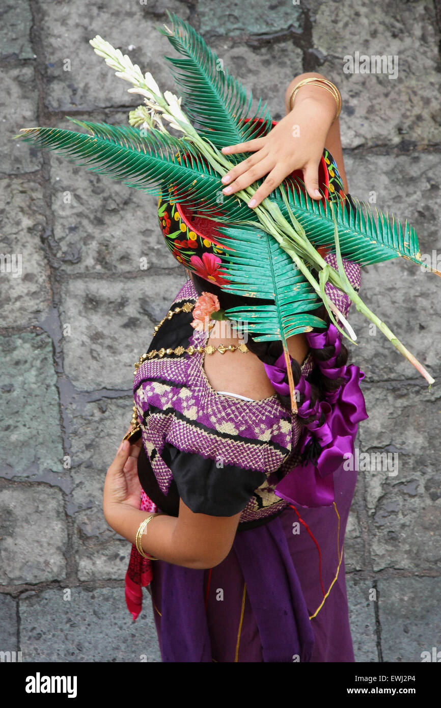 Mexican woman in traditional costume holding palm leaves - Stock Image