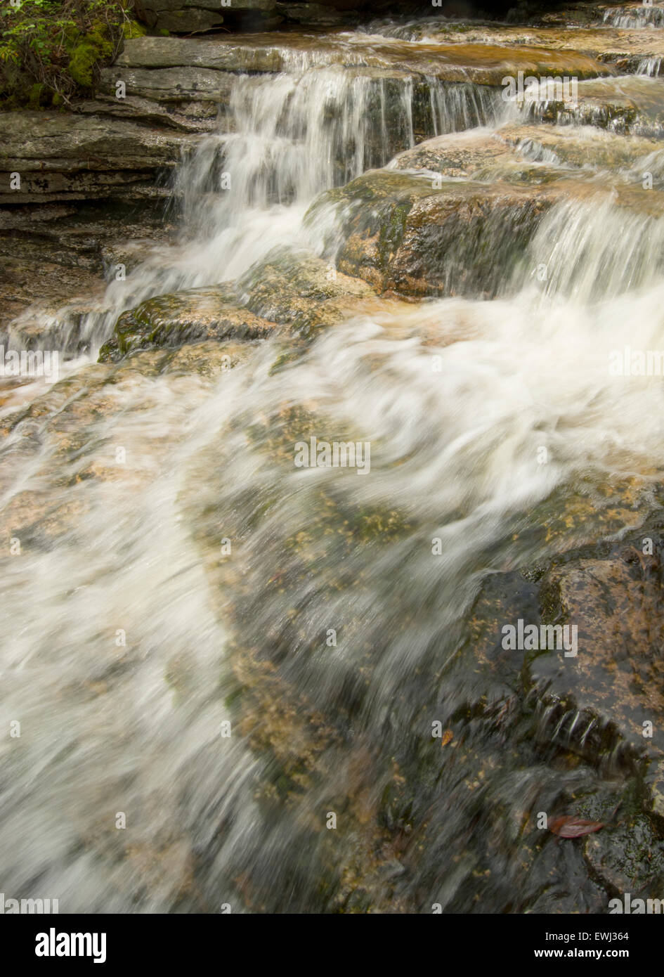 rushing stream through granite boulders after summer storm - Stock Image