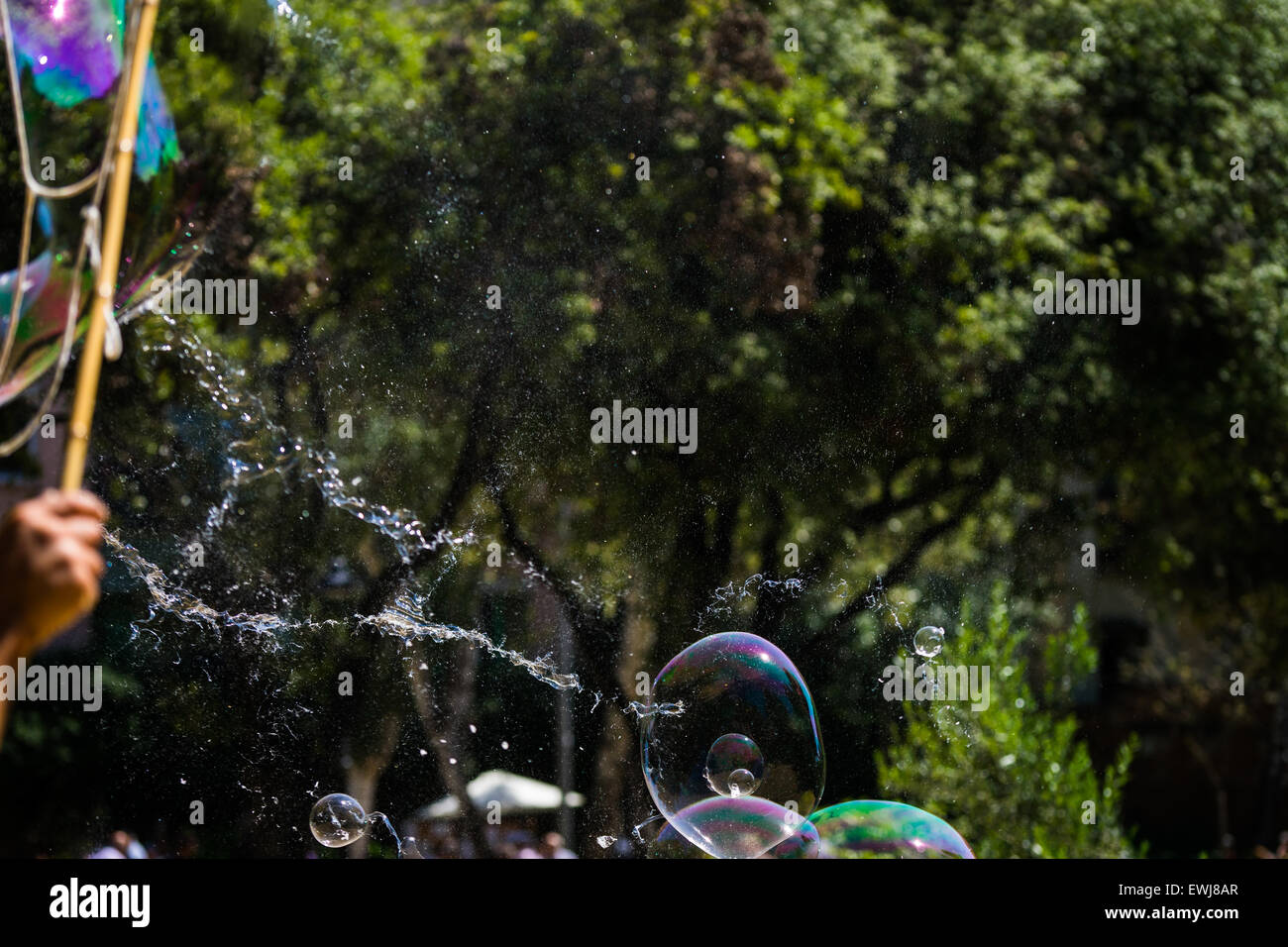 A big bubble bursting in a park in Barcelona. - Stock Image