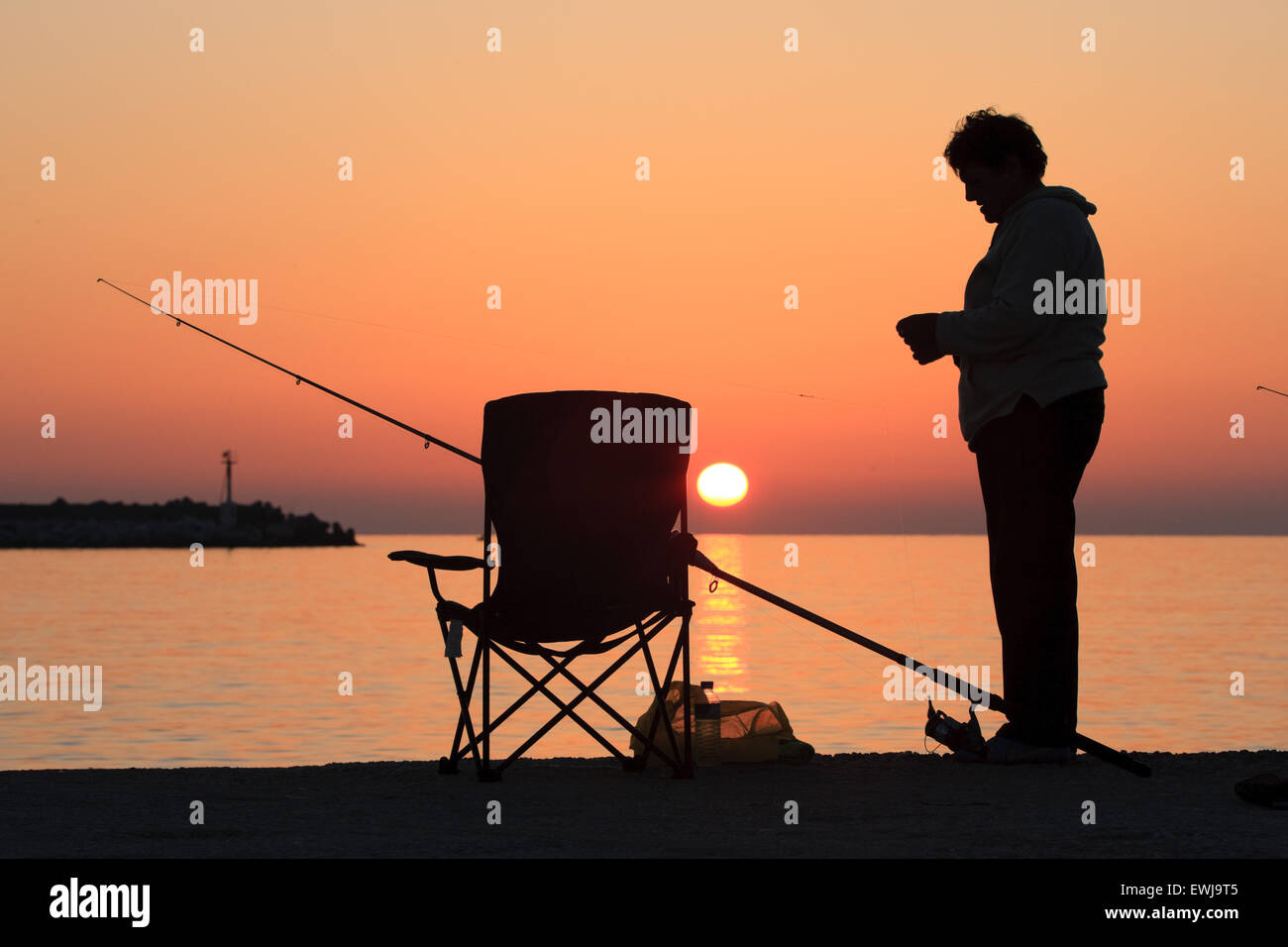 Woman in silhouete prepares fishing bait. Myrina city sunset. Lemnos / Limnos island, Greece/ Hellas. Copy space - Stock Image