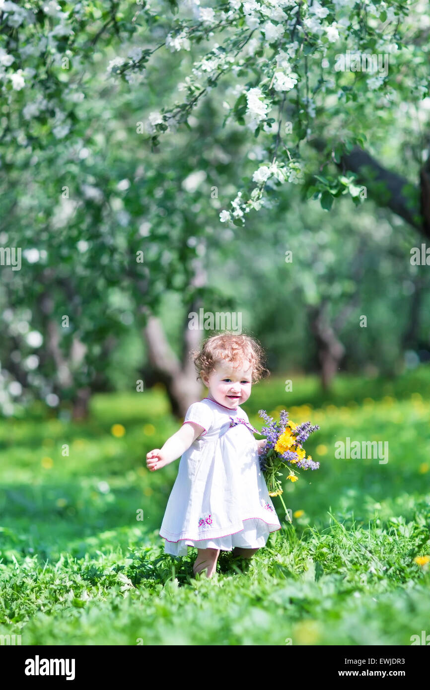sweet baby girl playing with beautiful flowers stock photo: 84613847