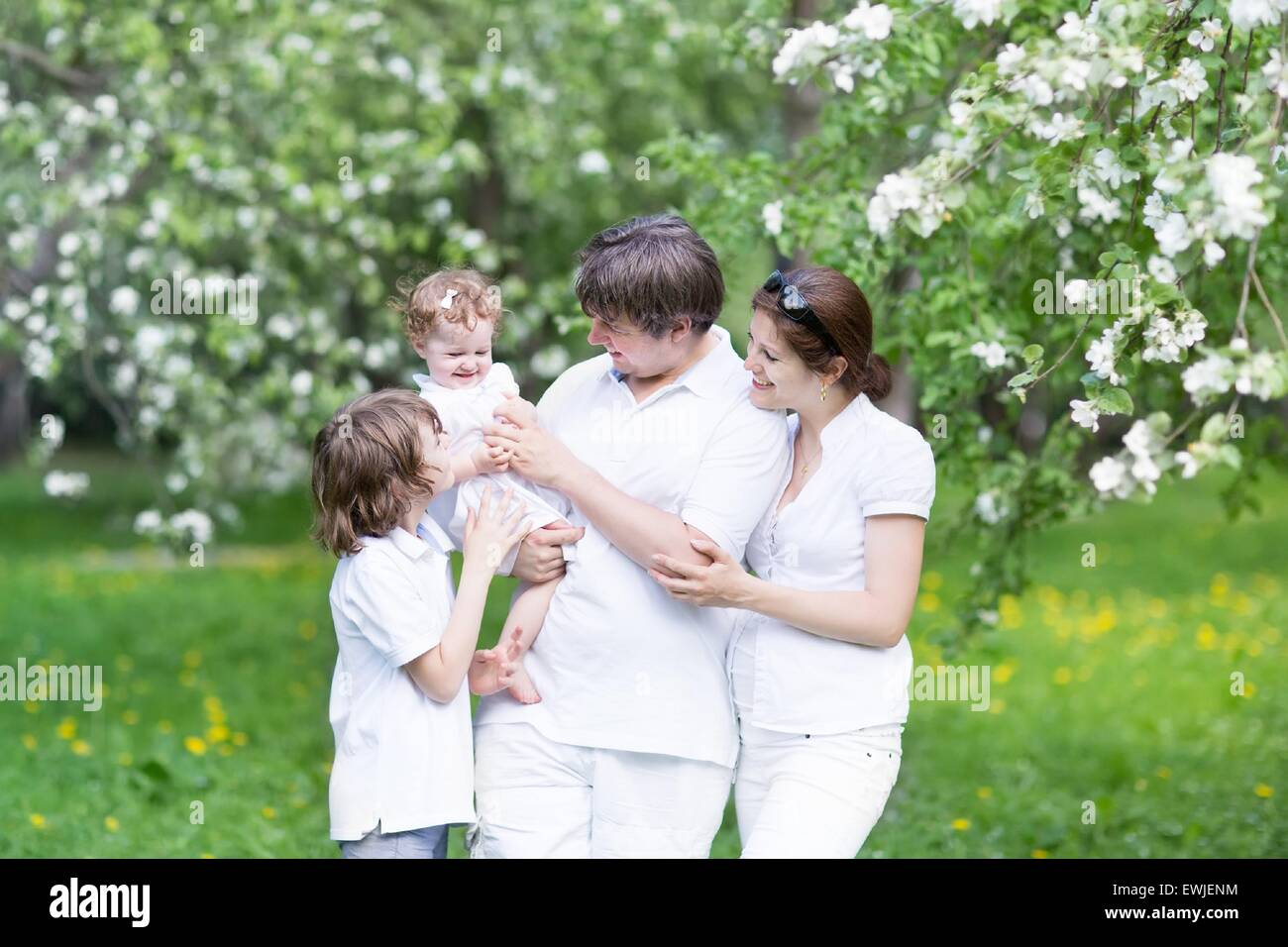 Happy young family in a blooming apple tree garden - Stock Image
