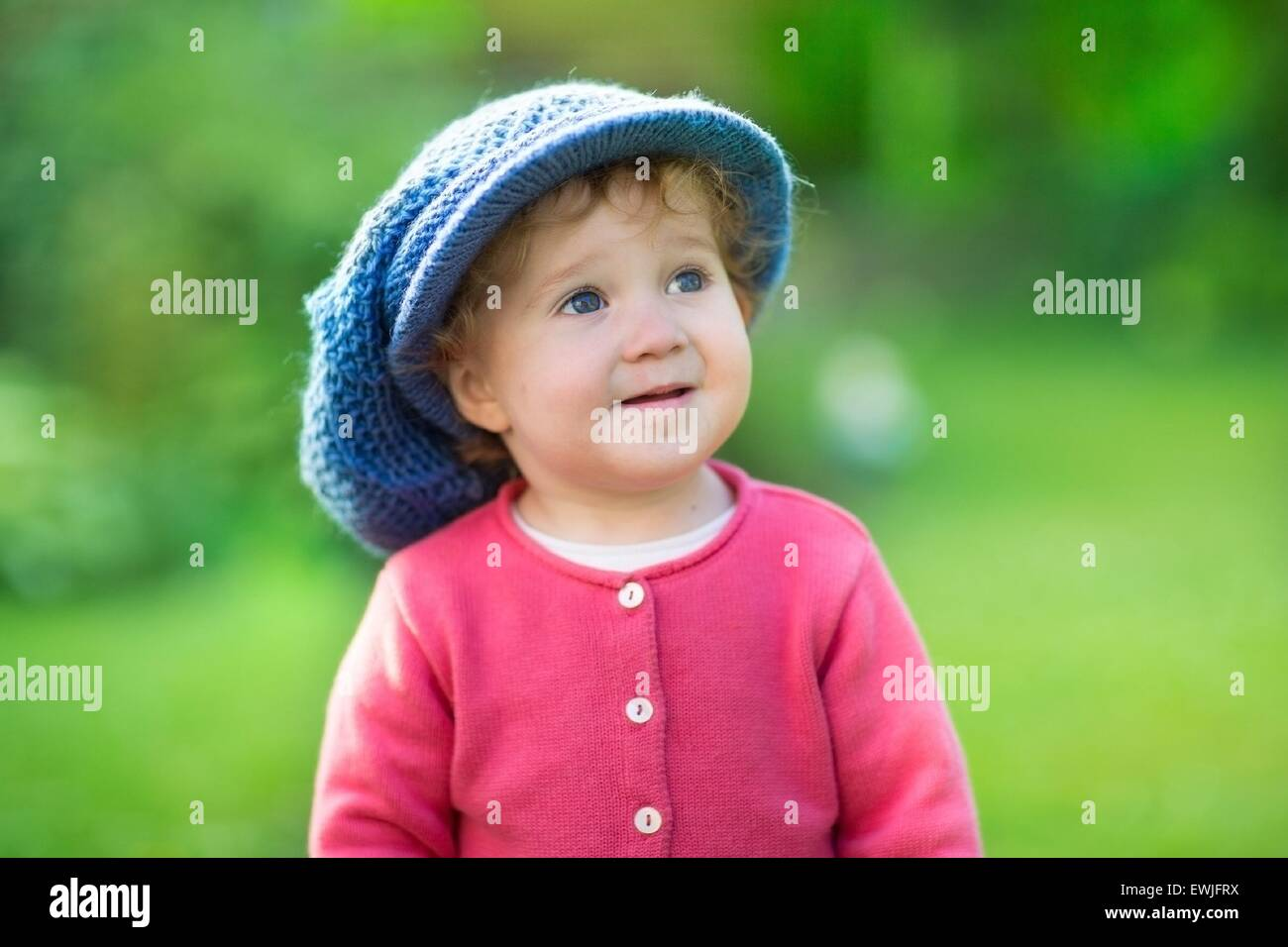 1c6a2c22e8a Funny baby girl wearing a big knitted hat playing in a sunny garden on a  warm autumn day