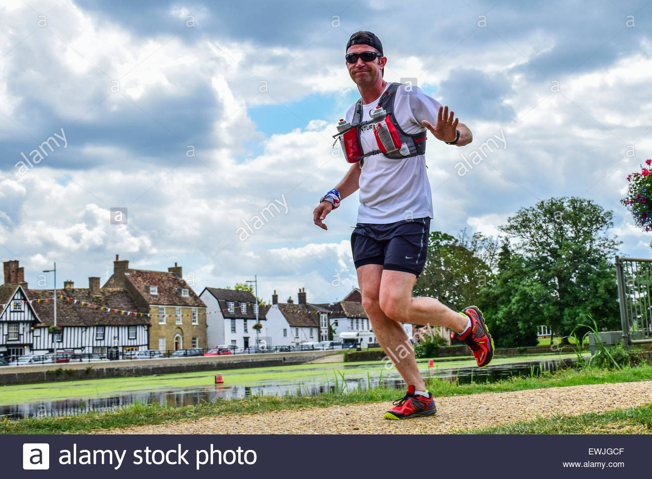 Godmanchester, Cambridgeshire, UK. 27th June, 2015. Darren Hancocks runs by the river with the landmark building - Stock Image
