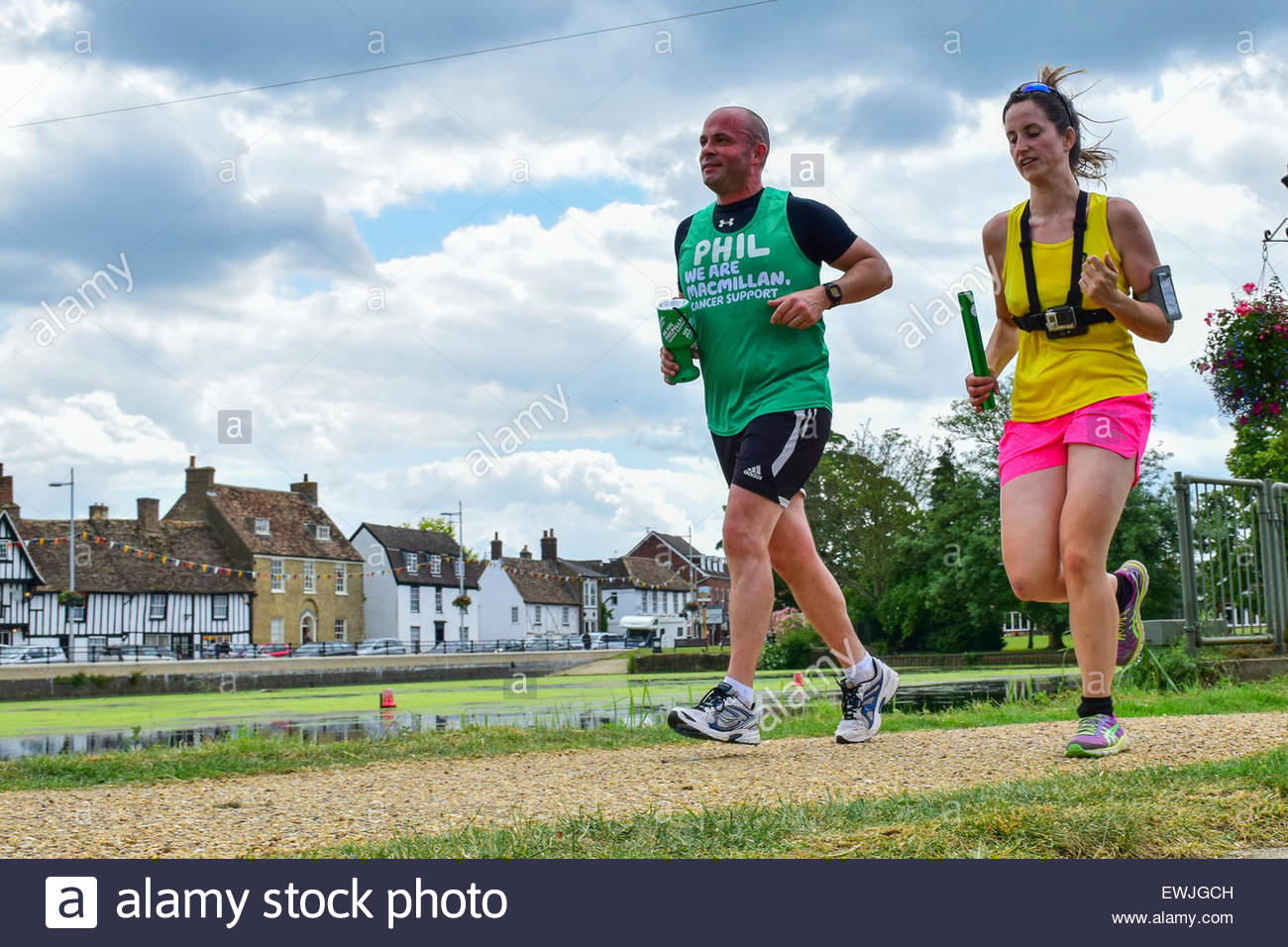 Godmanchester, Cambridgeshire, UK. 27th June, 2015. Runners pass the river with the Causeway in the background in - Stock Image