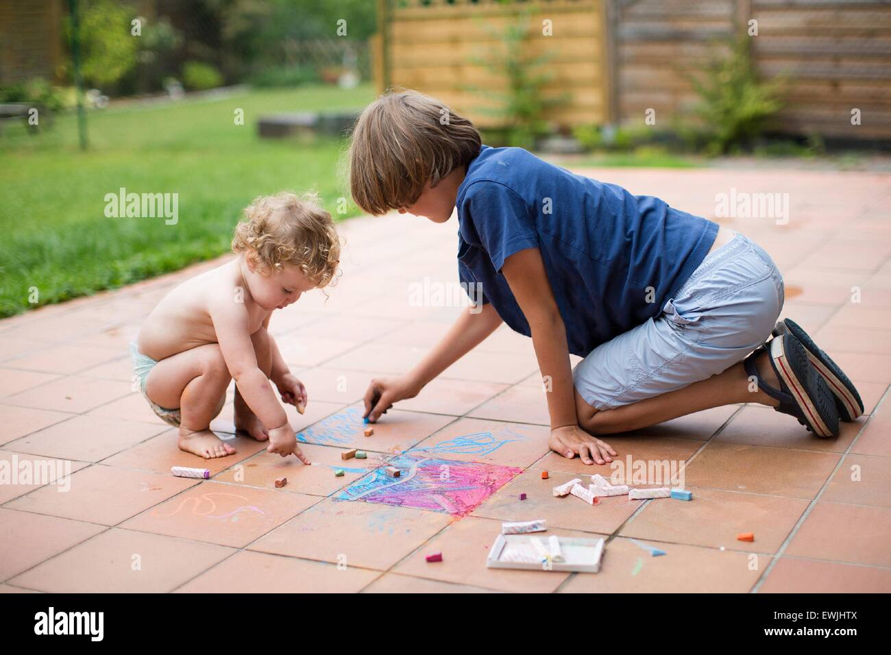 Brother and his baby sister playing together in the backyard painting with colorful chalk - Stock Image