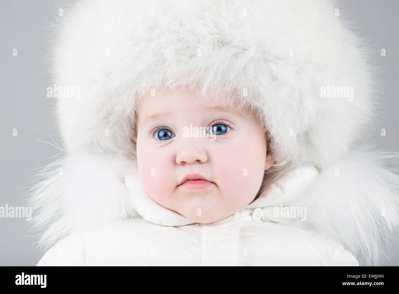 Funny sweet baby girl wearing a big fur hat and a white winter snow suit on light  blue background 1741e0973c4b