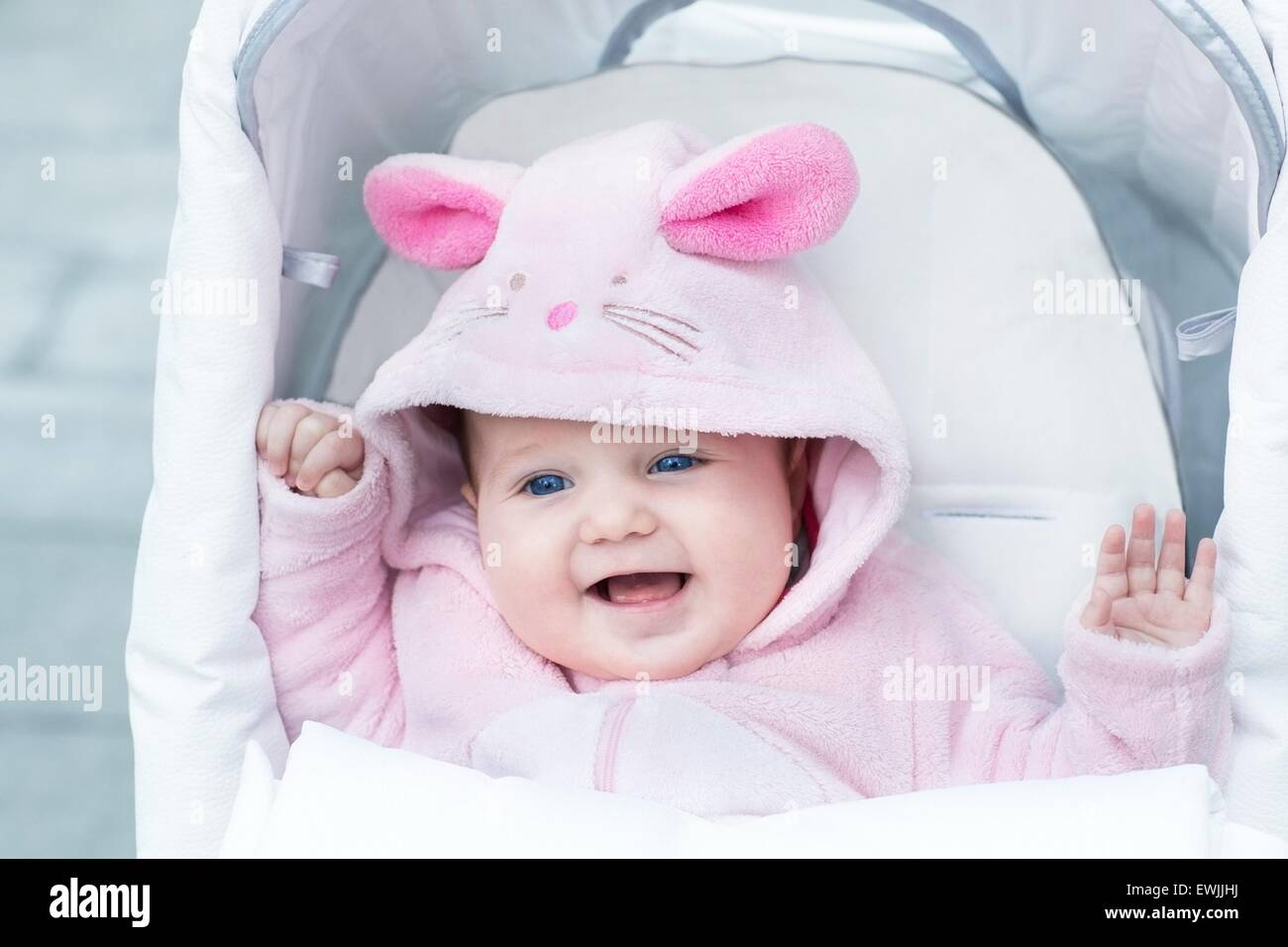 0c70d4901 Cute laughing baby girl enjoying a stroller ride on a cold winter day  wearing a warm
