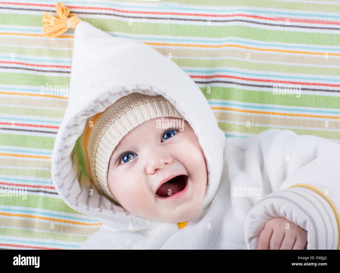 e584915e3 Cute funny laughing baby girl relaxing on a colorful blanket wearing ...