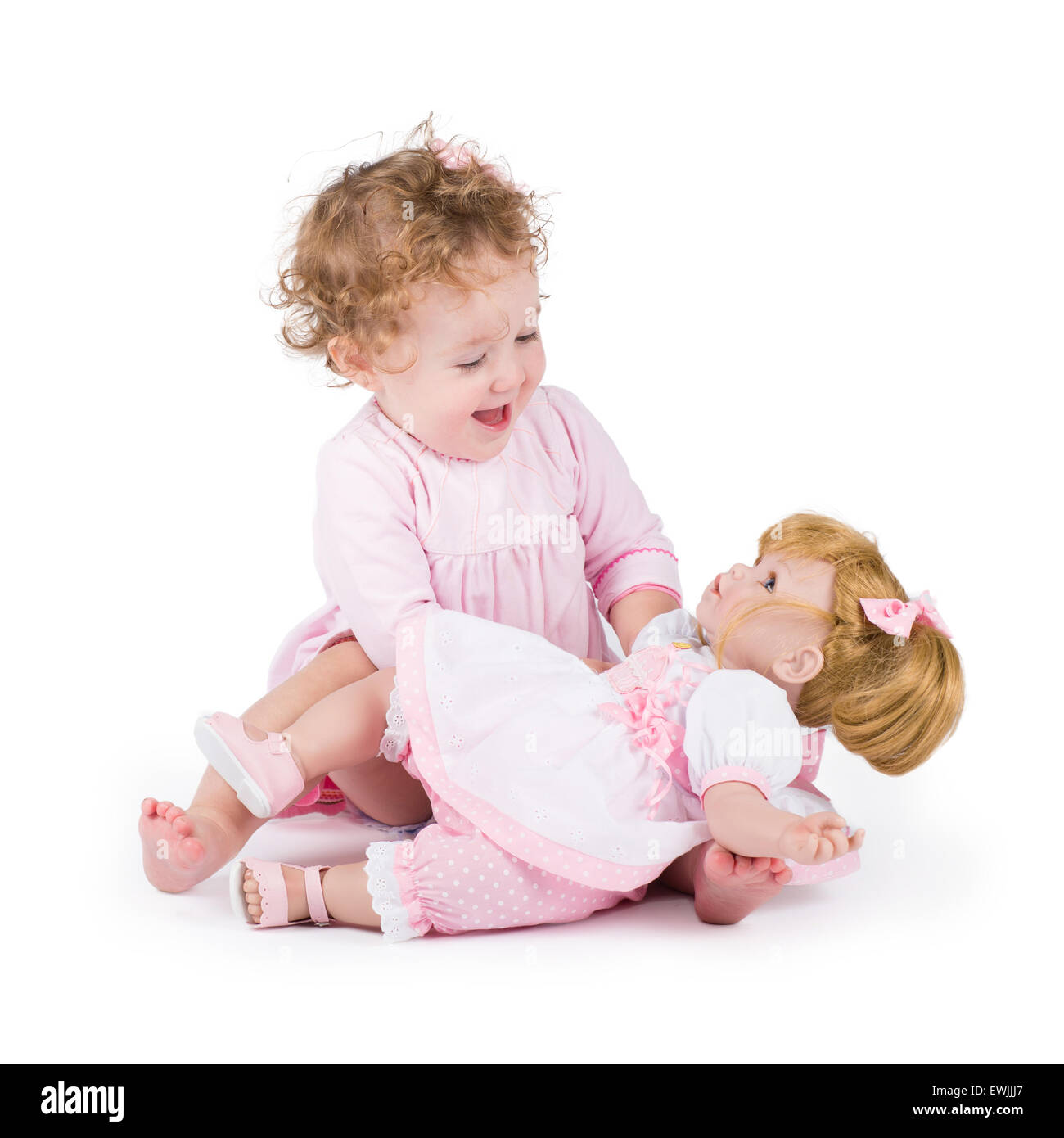 Funny little girl playing with a beautiful doll - Stock Image