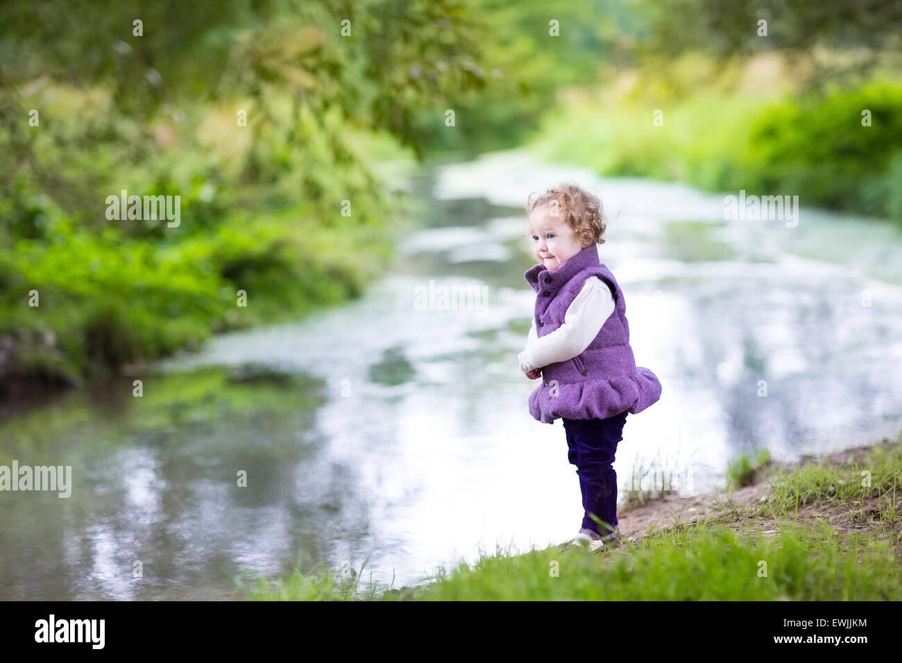 Beautiful little baby girl walking on a river shore on a nice autumn day - Stock Image