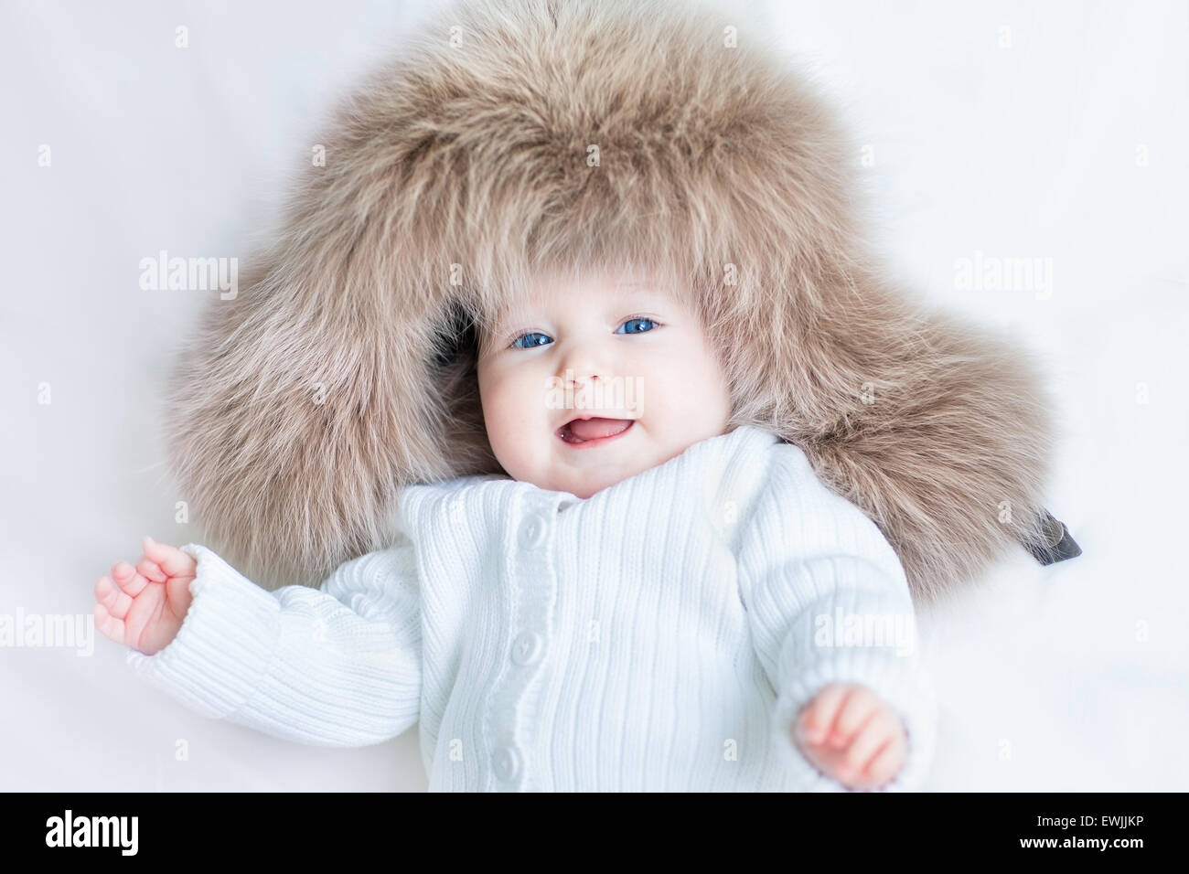 c3f7fd3dd Funny cute baby girl with big blue eyes wearing a huge winter hat ...