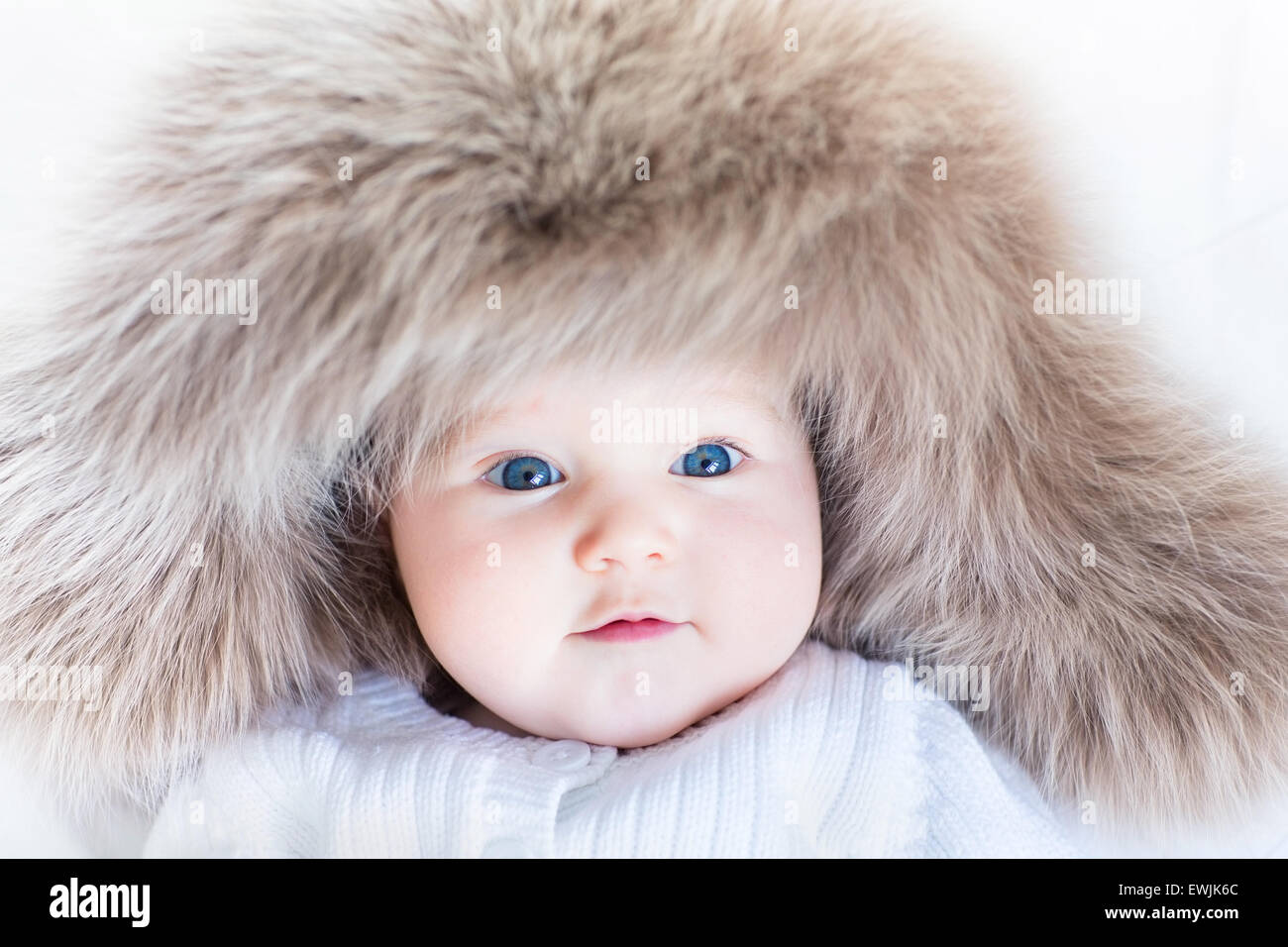 05b1fa0cf Funny cute baby girl with big blue eyes wearing a huge winter hat ...