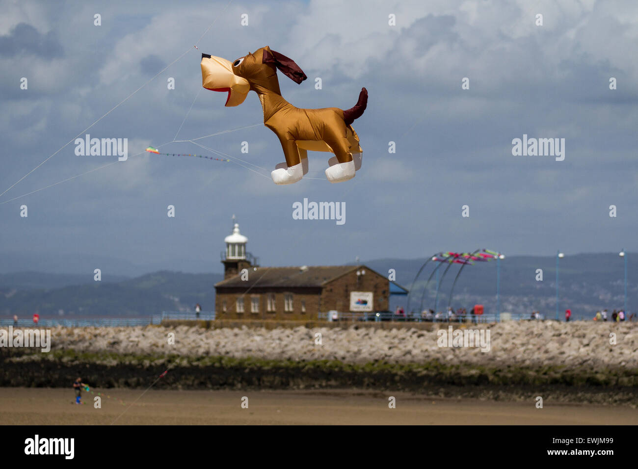 Morecambe, Lancashire, UK 27th June, 2015. Inflatable comical cartoon dog flying over the Stone Jetty Light house. Catch The Wind Kite Festival an annual festival on Morecambe seafront, when for the whole day the skies are full of the most spectacular shapes, colours and flying creations.  Featured were animal kites of all kinds and sizes. Stock Photo