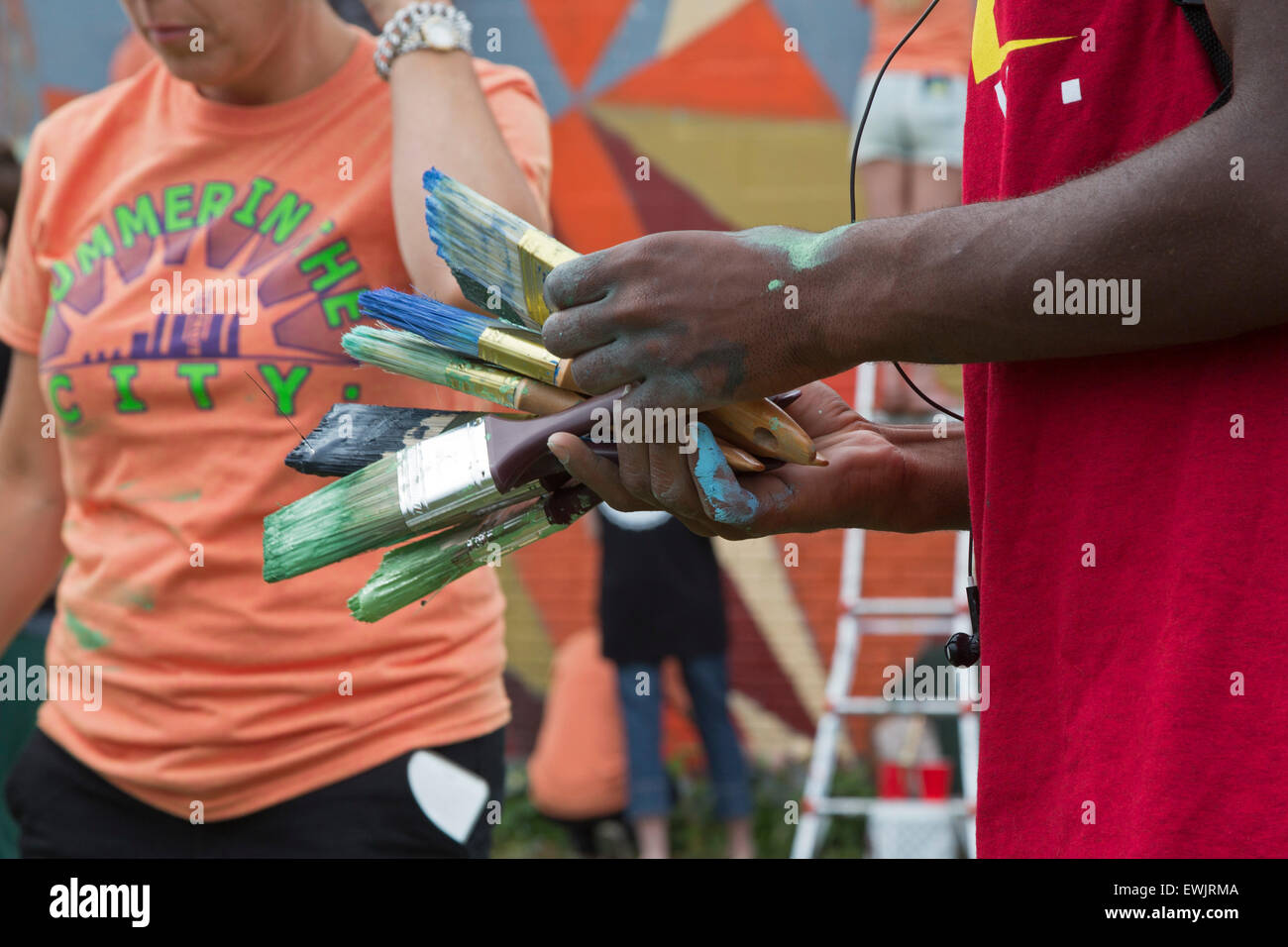 Detroit, Michigan - Young adults clean brushes after painting a mural in southwest Detroit. - Stock Image
