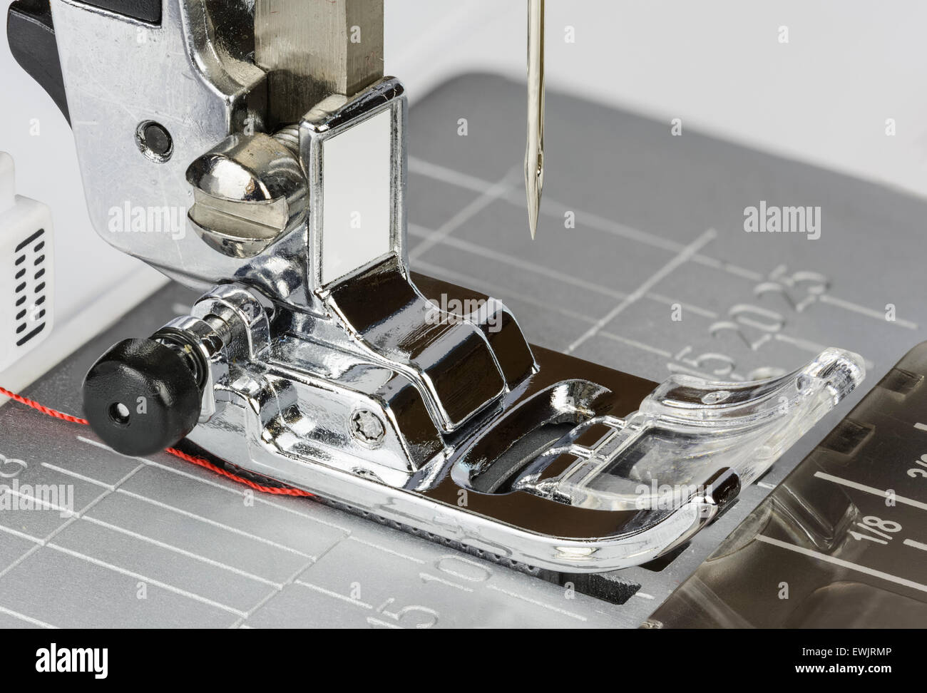 Closeup of the presser foot and needle of an electric sewing machine. - Stock Image