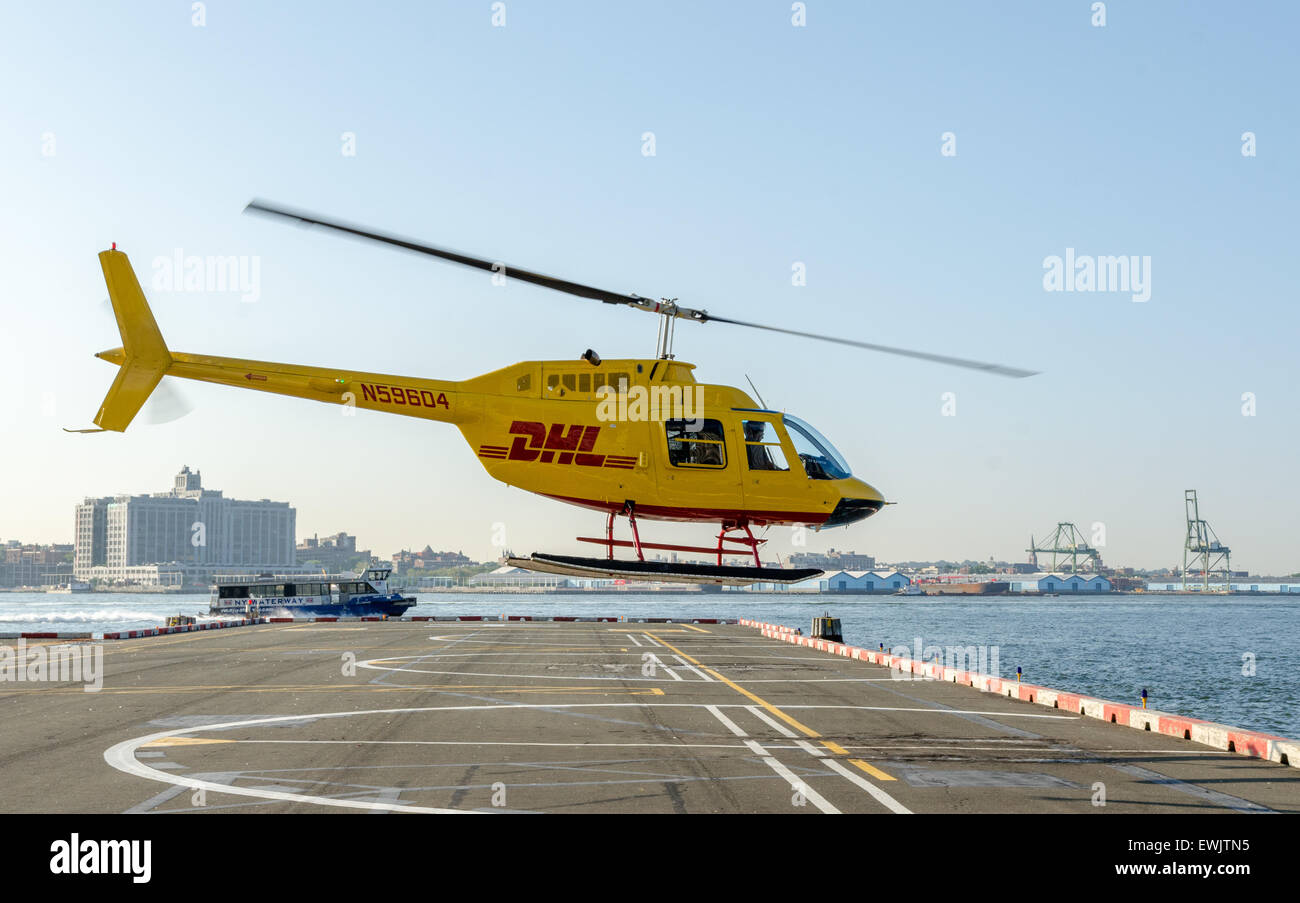 Bell 206 helicopter in DHL colours taking off from Wall Street Heliport in Manhattan, New York - Stock Image