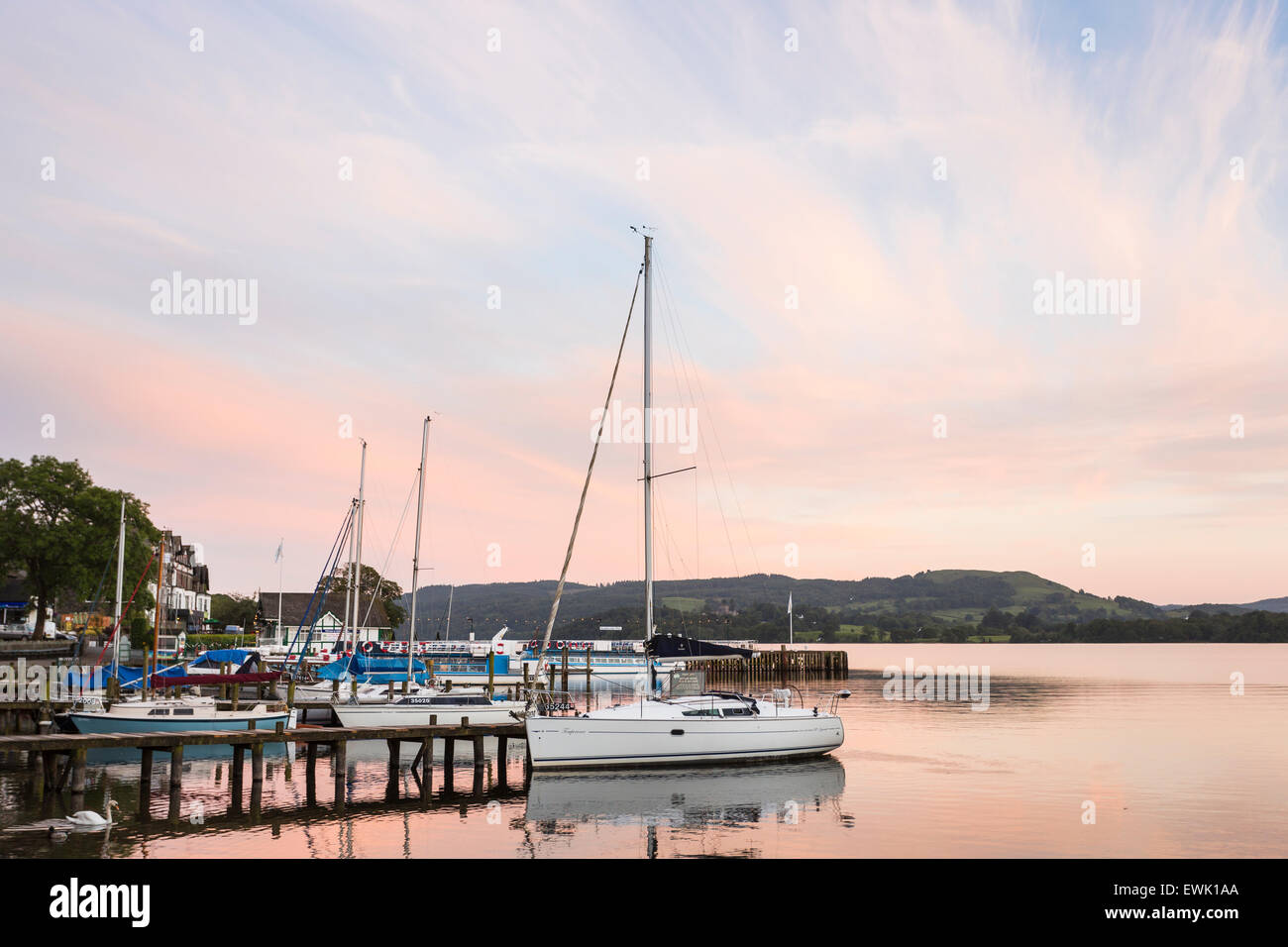 Boats (yachts) moored at Ambleside Pier, Waterhead, Lake Windermere, English Lake District, Cumbria in early evening - Stock Image
