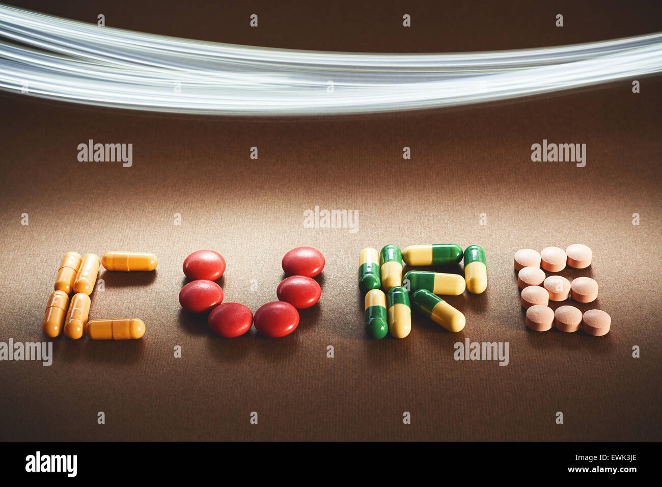 Word cure written with various different pills and tablets, lighting effect in upper side of image. - Stock Image