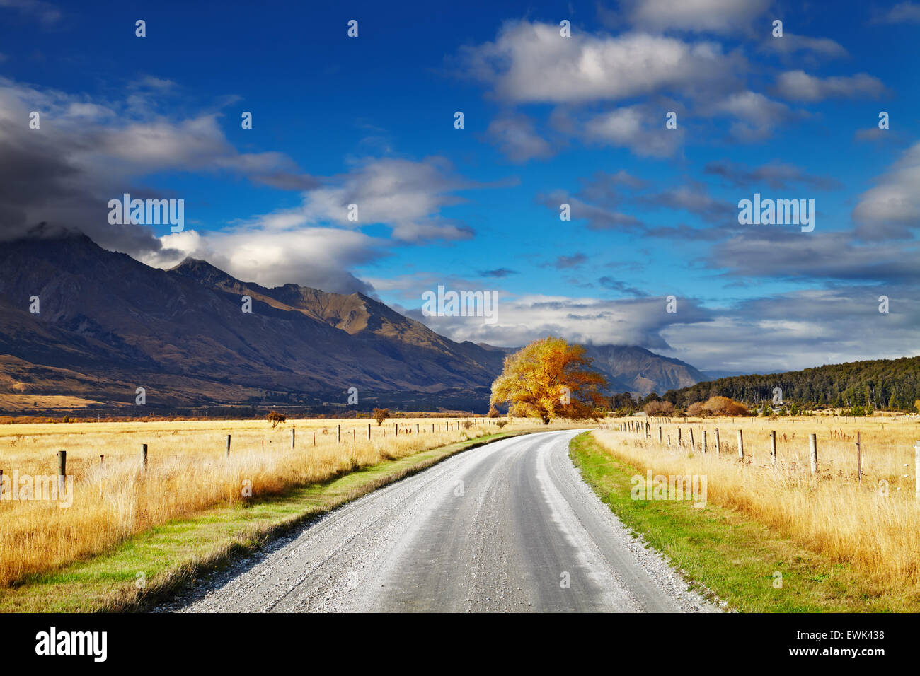 Mountain landscape with road and blue sky, Otago, New Zealand - Stock Image