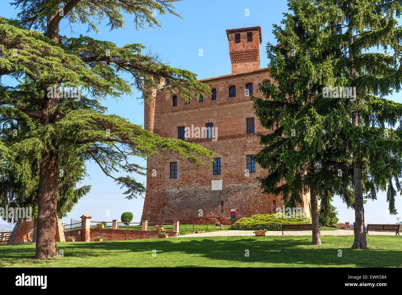 Small green lawn, trees and medieval castle in Piedmont, Northern Italy. - Stock Image