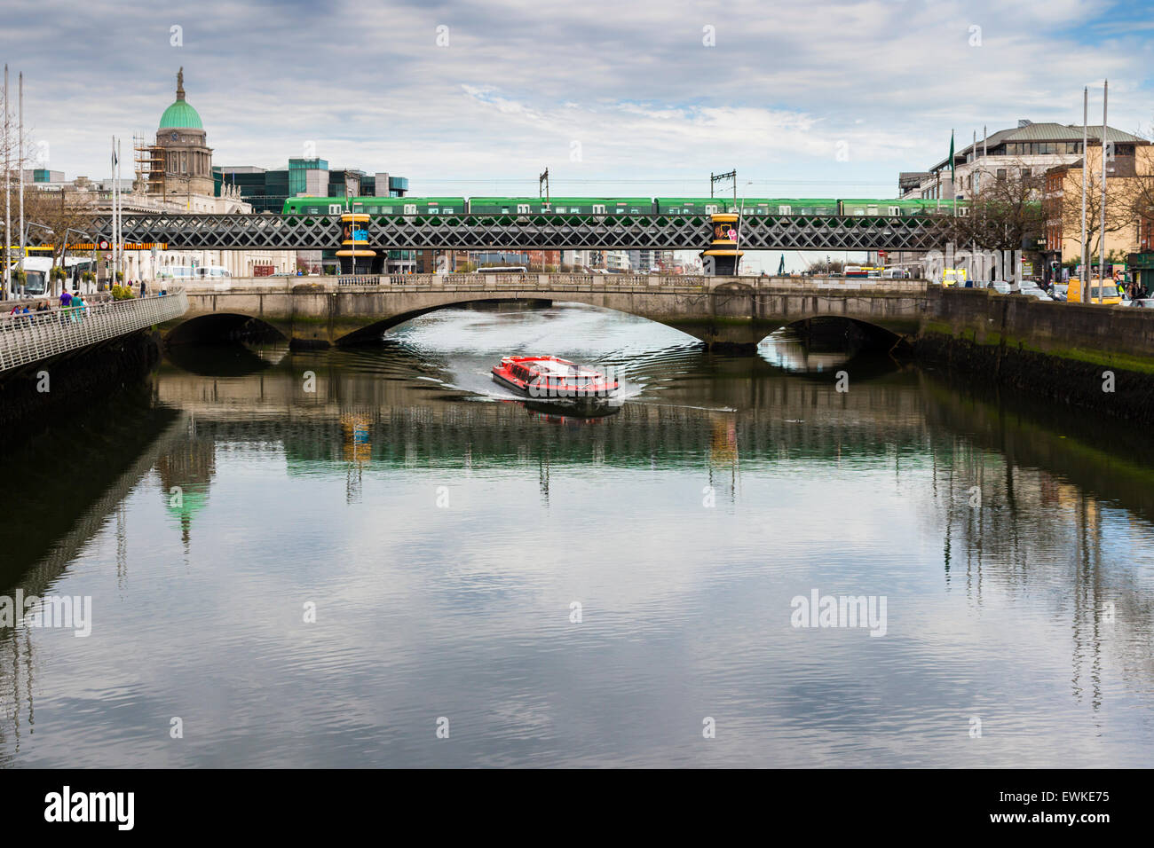 Dublin Tour Boat passes underneath the Rosi Hacket Bridge on the Liffey. - Stock Image